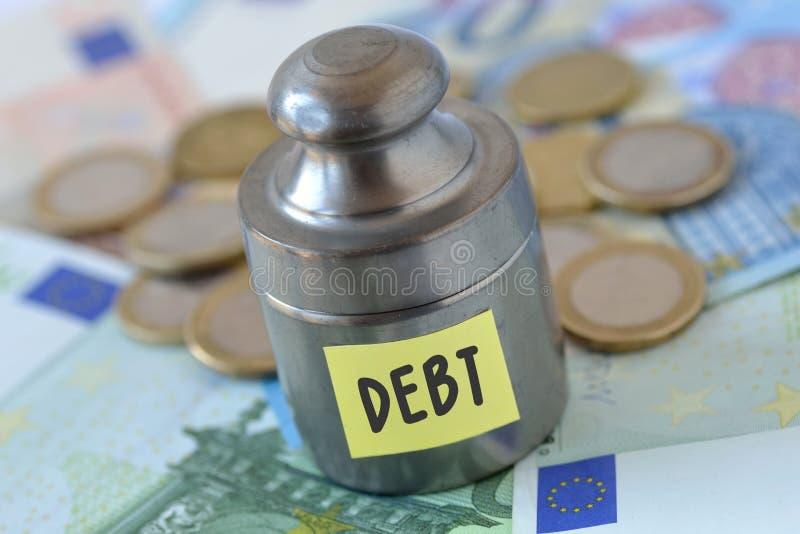 Вес с задолженностью слова написанной на бумажном примечании на банкноте евро стоковое изображение rf