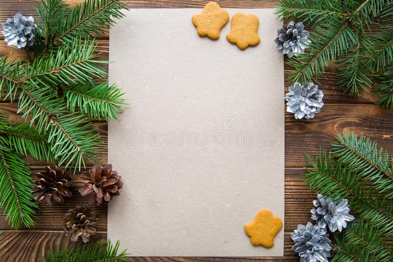 Ветви ели, конусы серебра сосны и печенья пряника колоколообразные на коричневом деревянном столе звезды абстрактной картины конс стоковая фотография