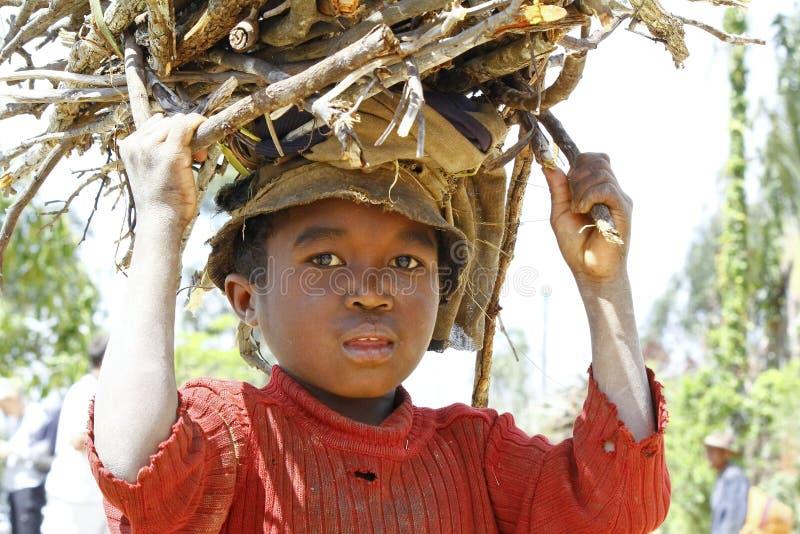 Ветви нося плохого малагасийского мальчика на его голове стоковая фотография rf