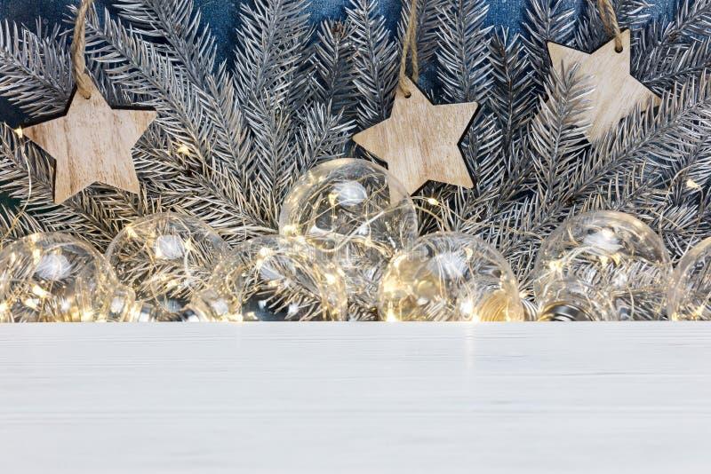 Ветви рождественской елки, деревянные звезды и garl старого света накаляя стоковые изображения