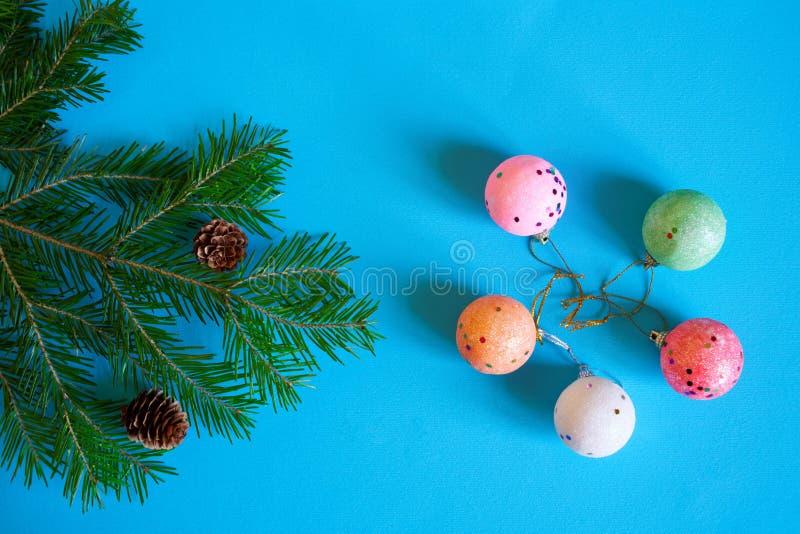 Ветвь рождественской елки, конусов и красочных шариков на голубой предпосылке С Рождеством Христовым и с новым годом стоковая фотография