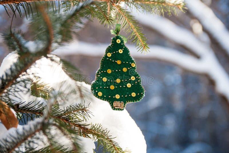 Ветвь рождественской елки в лесе с зеленым handmade украшением стоковое фото rf