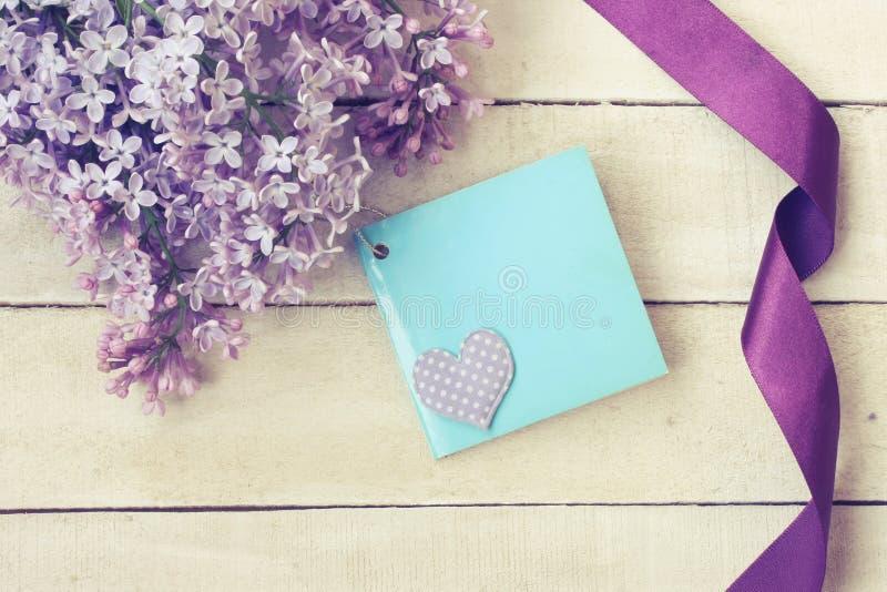 Ветвь сирени, silk фиолетовой ленты, карточки поздравлению стоковое изображение