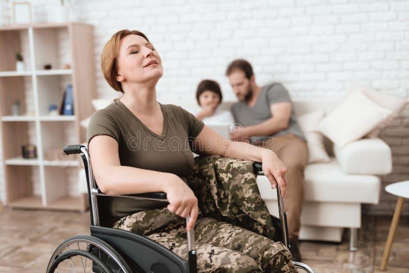 Ветеран женщины в кресло-коляске возвращенной от армии Она расслабляющая и близка она глаза стоковое изображение rf