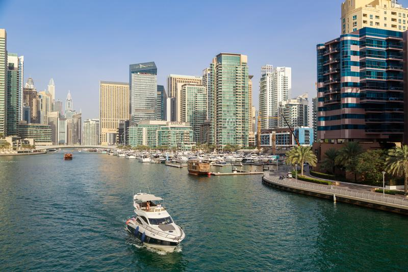 Ветрила яхты мотора на заливе на фоне современных зданий в районе Марины Дубай стоковое изображение