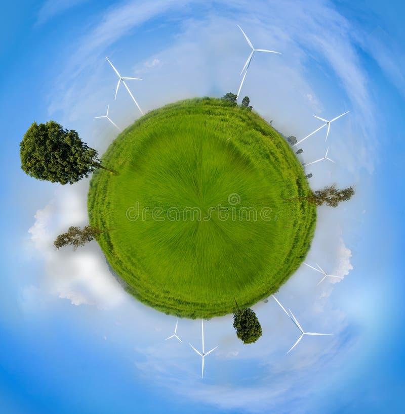 Ветротурбина создателя силы Eco влияния sphre глобуса электрическая в свежем зеленом поле против голубого неба стоковое изображение