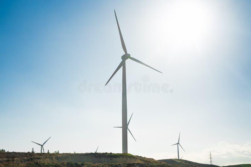 Ветротурбина для альтернативной энергии ветер турбины силы штепсельной вилки панели удерживания руки зеленого цвета eco принципиа стоковые фото