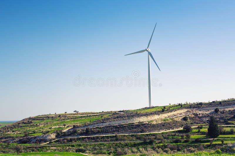Ветротурбина для альтернативной энергии ветер турбины силы штепсельной вилки панели удерживания руки зеленого цвета eco принципиа стоковое фото