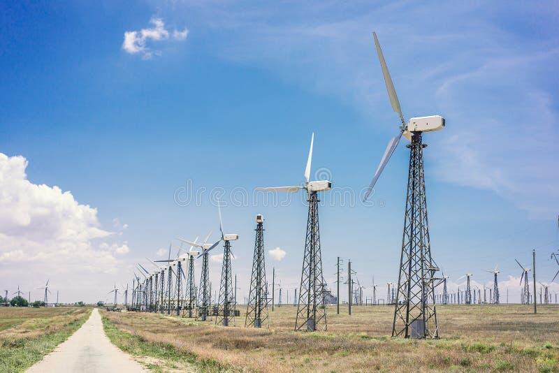 Ветротурбины которые производят электричество в полях Европы стоковая фотография rf
