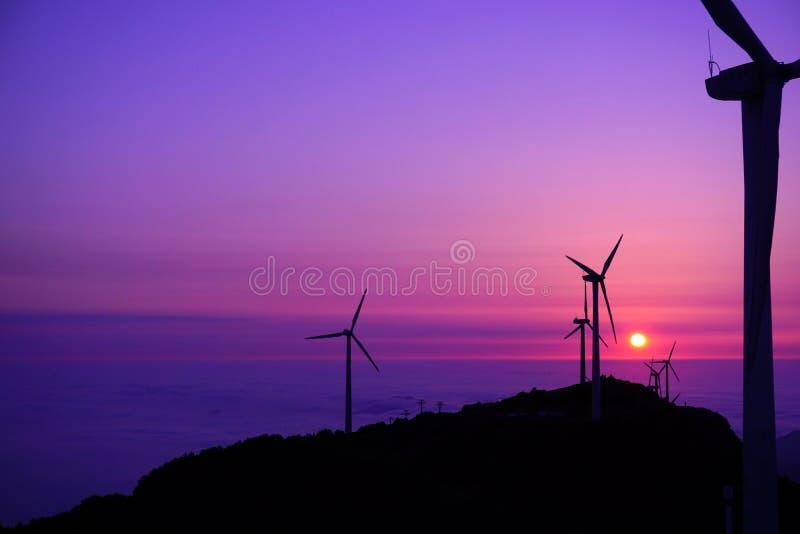 Ветротурбины на горах на заходе солнца стоковые изображения