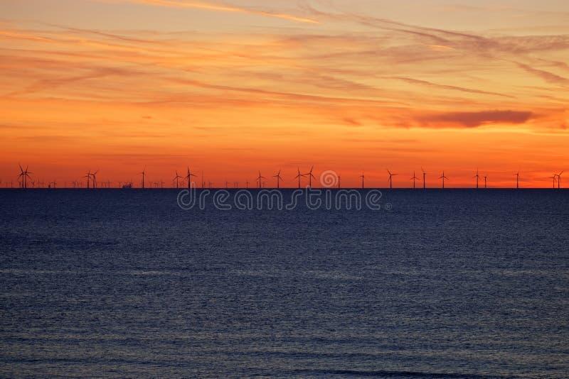 Ветроферма на море на закате стоковое изображение rf
