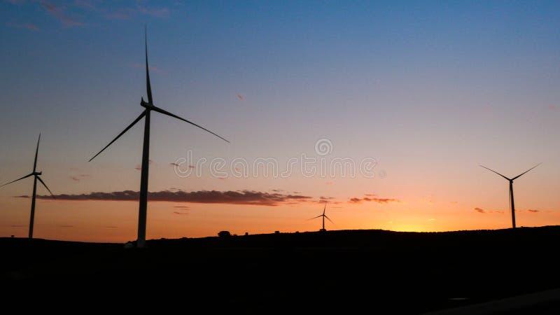 Ветрянка энергии ветра захода солнца турбин стоковая фотография