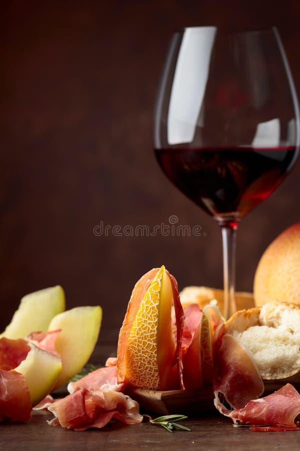 Ветчина с дыней и розмариновым маслом на старом деревянном столе стоковая фотография