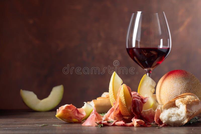 Ветчина с дыней и розмариновым маслом на старом деревянном столе стоковая фотография rf