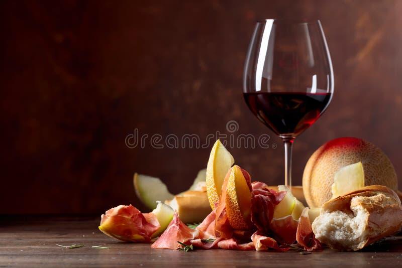 Ветчина с дыней и розмариновым маслом на старом деревянном столе стоковые фото