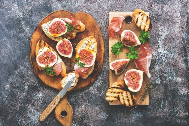 Ветчина с смоквами Свежие смоквы с ветчиной и сыром на разделочной доске, деревенской предпосылкой аппетитная заедк Взгляд сверху стоковая фотография rf
