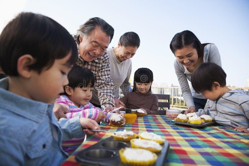 Вечеринка по случаю дня рождения, семья мульти-поколения, сидя на таблице стоковые фото
