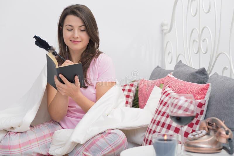 Вечер в кровати с книгой стоковое фото