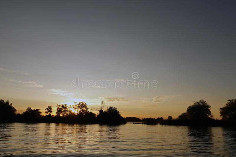Вечер лета с голландским заходом солнца ветрянки на водах около Grou во Фрисландии стоковое фото rf