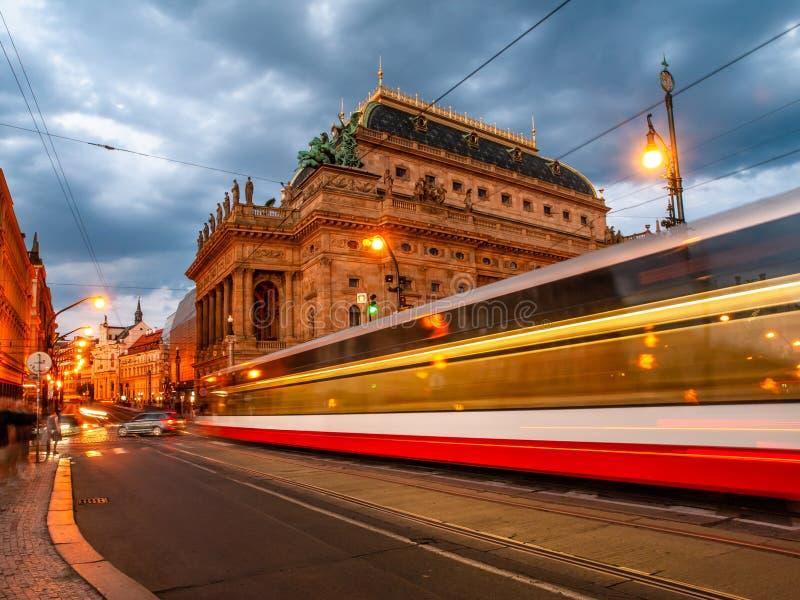 Вечер на национальном театре и запачканном трамвае на мосте, Праге, чехии Съемка долгой выдержки стоковое фото rf