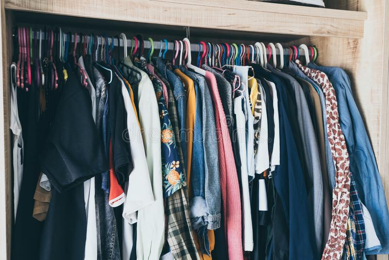 Вешалки с различными одеждами в шкафе шкафа стоковое фото