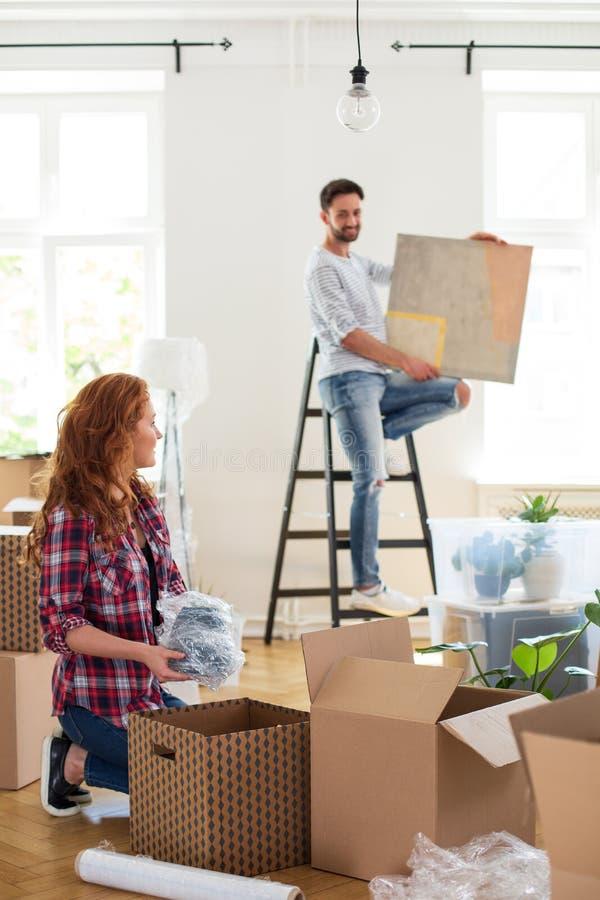 Вещество и человек упаковки женщины с картиной на лестнице в запачканной предпосылке двигая вне от дома стоковое фото rf