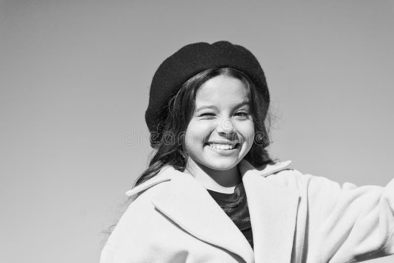 Вещи идя быть alright Девушка подмигивает жизнерадостной стороне предпосылке голубого неба Удовлетворенное шляпы и пальто носки д стоковая фотография