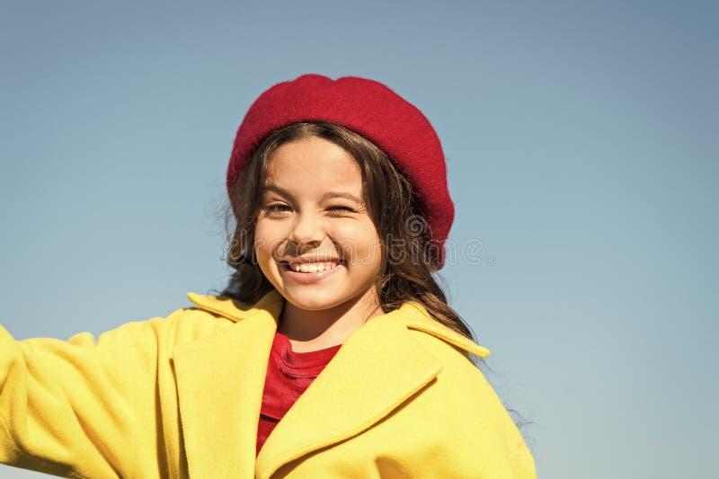 Вещи идя быть alright Девушка подмигивает жизнерадостной стороне предпосылке голубого неба Удовлетворенное шляпы и пальто носки д стоковое изображение rf