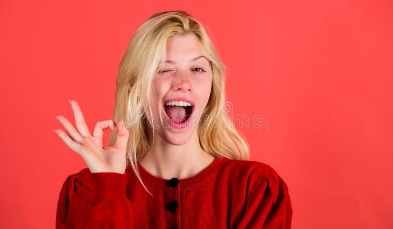Вещи идя быть alright Девушка подмигивает счастливой стороне пока жест ок шоу над красной предпосылкой Женщина удовлетворяемая со стоковое фото