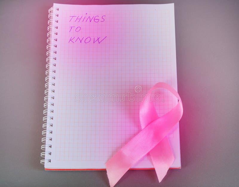 Вещи, который нужно знать написаны в блокноте с розовым раком молочной железы осведомленности ленты стоковое изображение