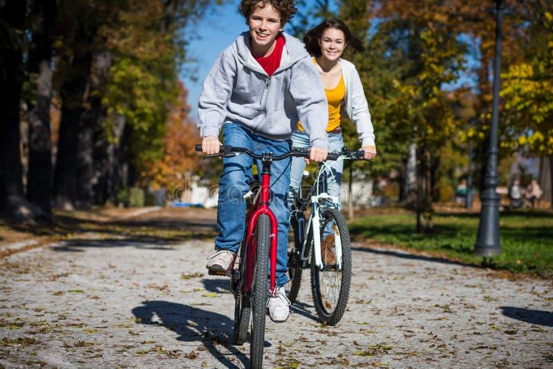 Велосипед девочка-подростка и мальчика стоковое изображение rf