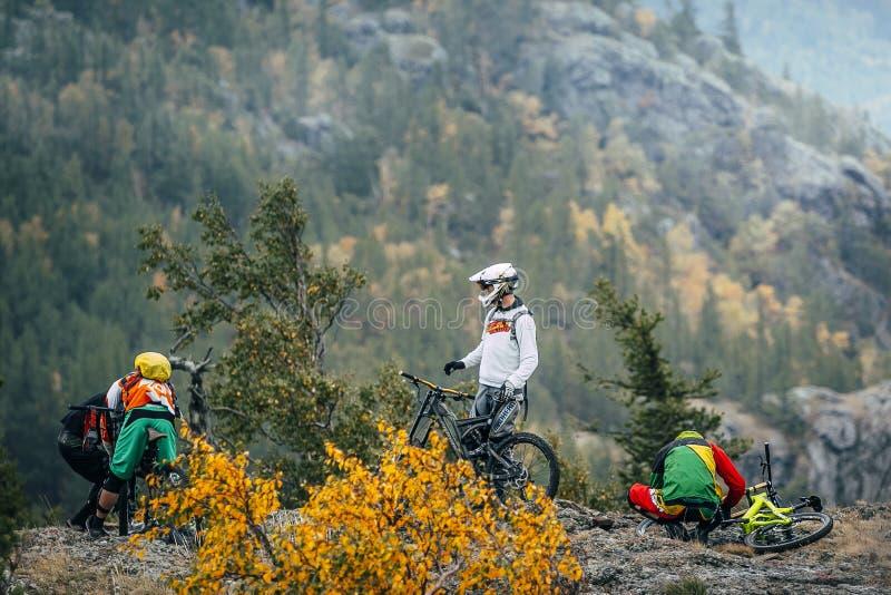 Велосипедисты горы гонщиков подготовки к покатому стоковое фото