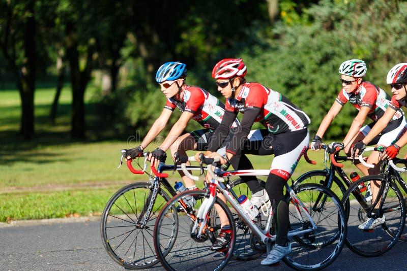 Велосипедисты ехать велосипеды на улице стоковое изображение rf
