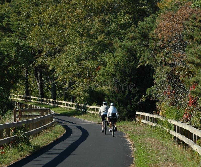 Велосипедисты на следе рельса трески накидки стоковая фотография rf