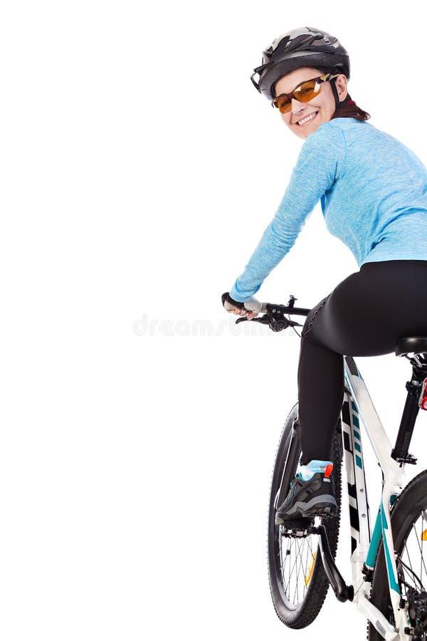 Велосипедист взрослой женщины ехать велосипед смотрит назад и усмехаться стоковое фото rf