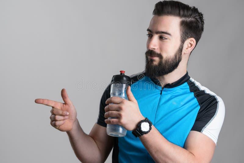 Велосипедист в голубой рубашке jersey держа пустой контейнер воды стоковое изображение