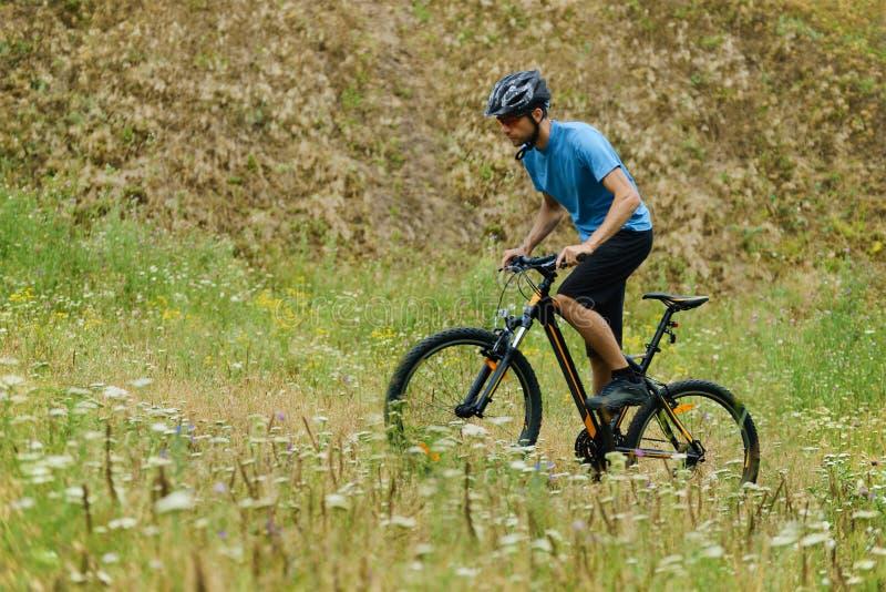 Велосипедист горы ехать его велосипед через лужок стоковые изображения rf