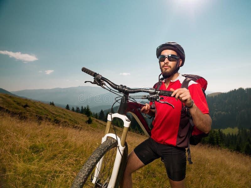 Велосипедист горы на луге стоковые изображения