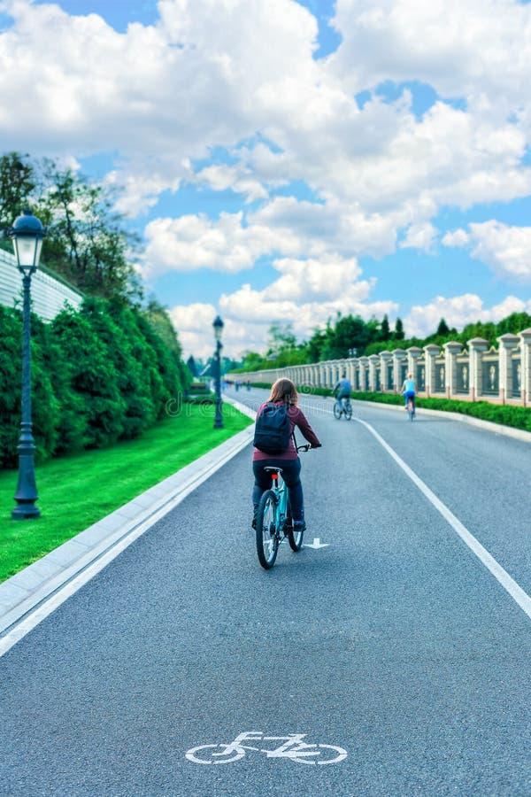 Велосипедист ехать велосипед на дороге к заходу солнца стоковое изображение
