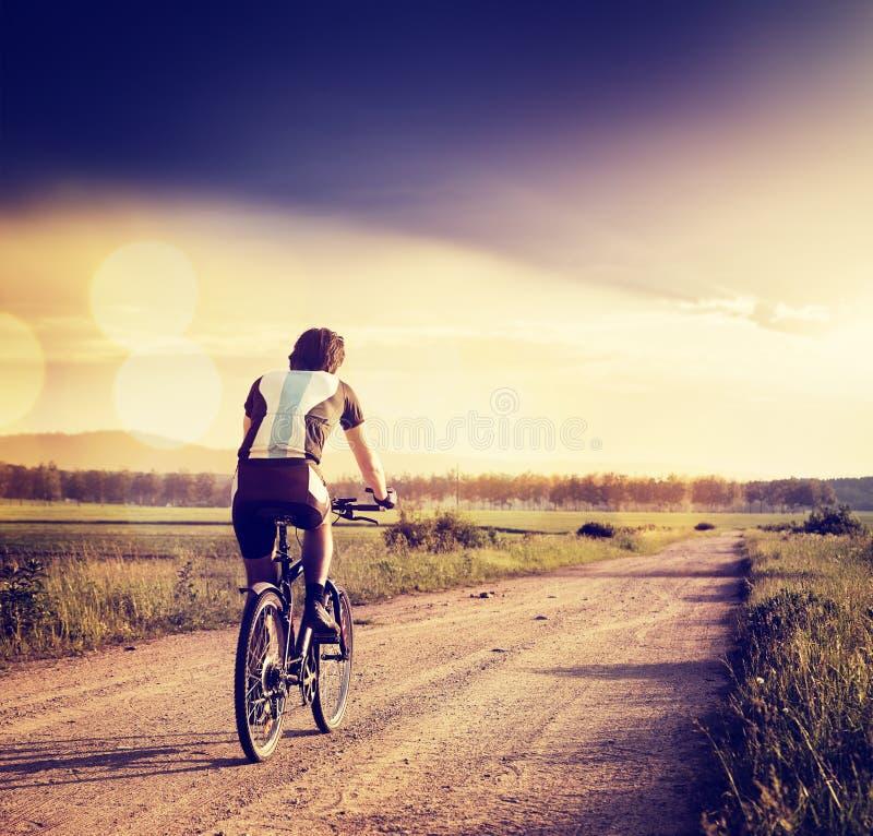Велосипедист ехать велосипед на проселочной дороге фото тонизировало стоковое изображение rf