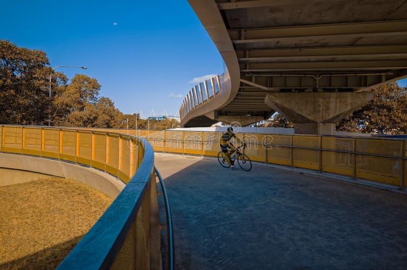 Велосипедист ехать вниз с спирального моста стоковое изображение