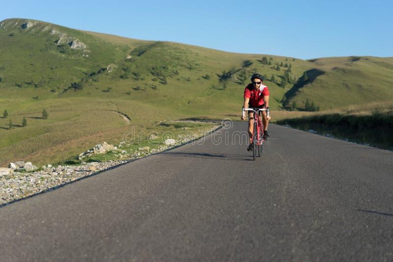 Велосипедист задействуя на дороге стоковое изображение rf