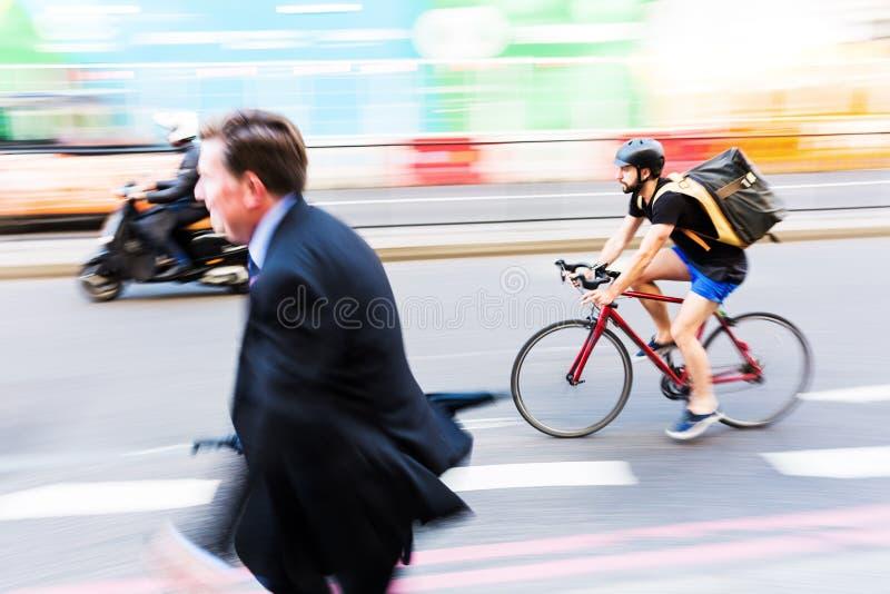 Велосипедист и бизнесмен в нерезкости движения в городском транспорте Лондона, Великобритании стоковое изображение