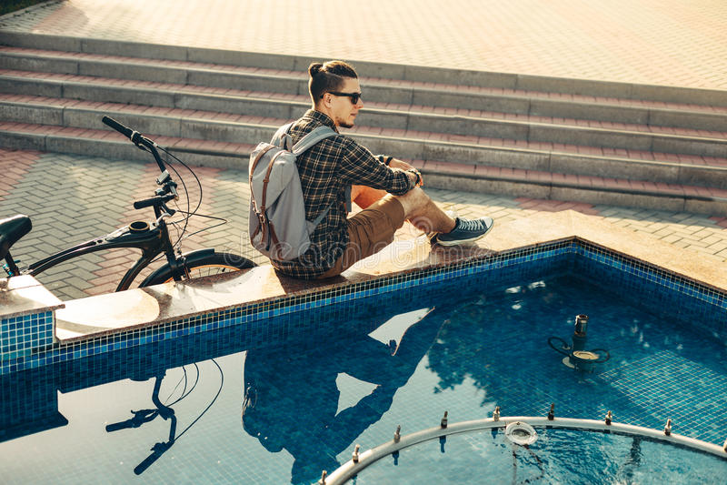 Велосипедист молодого человека сидя около фонтана рядом с велосипедом в концепции ежедневного образа жизни парка лета городской о стоковые фотографии rf