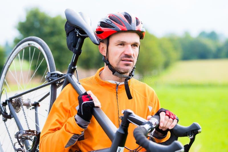Велосипедист нося его велосипед над плечом стоковая фотография rf