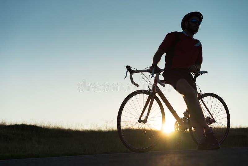 Велосипедист около его велосипеда дороги стоковое фото rf