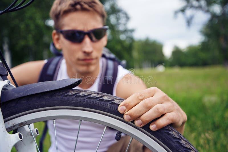 Велосипедист проверяет колесо стоковое изображение rf