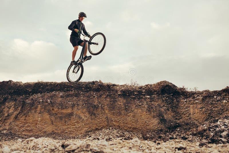 Велосипедист скача от утеса стоковое изображение