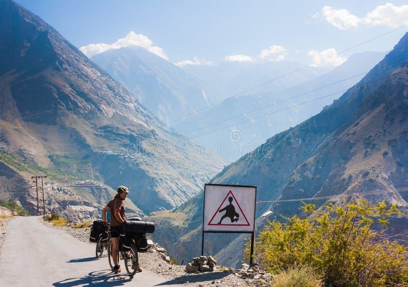 Велосипедист стоящий близко дорожный знак на дороге горы Гималаев стоковая фотография