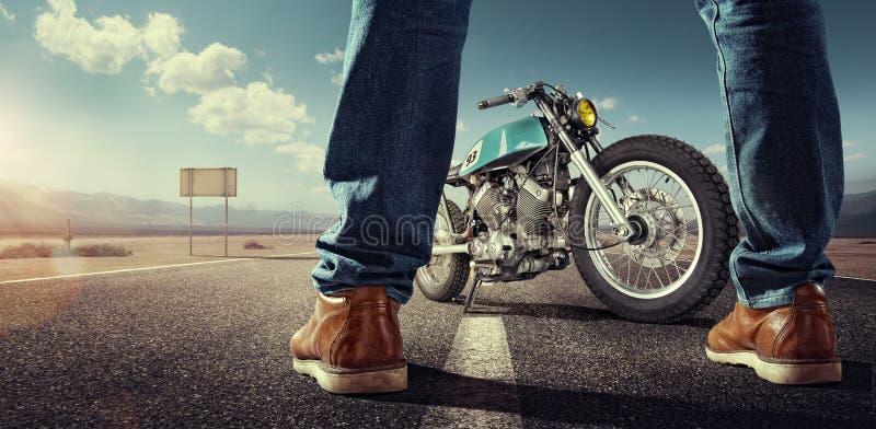 Велосипедист стоя около мотоцикла на пустой дороге стоковая фотография